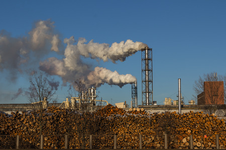 smoking chimneys wood processing plant on a background of blue sky Stock Photo