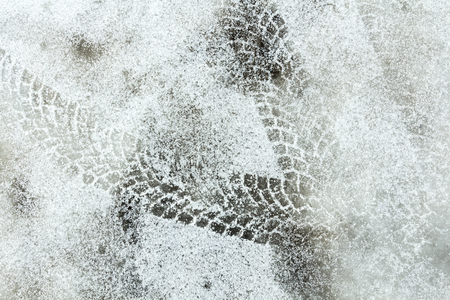 Shoe print and tyre track on a snow, abstract background