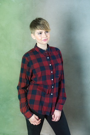 Teenager girl with short haircut concrete wall on background