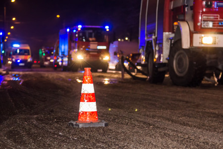 a cone on the road during the fire extinguishing in the winter in the evening on the background of fire trucks and ambulances Stock Photo