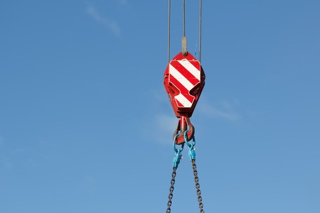 Mobile crane hook with chains, blue sky on background