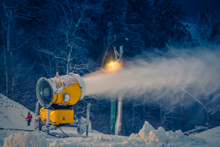 snow making machine on the hill producing snow on the ski run in the winter evening Stock Photo - 121890182
