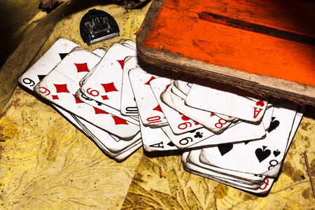 Old playing cards on dirty wooden surface Stock Photo