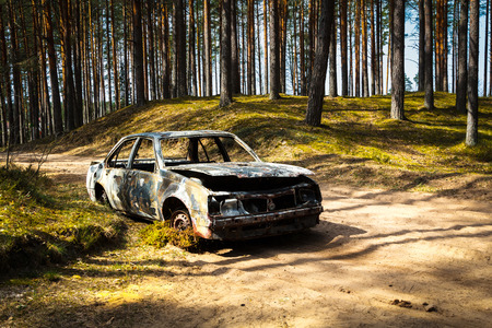 Fully burnt car in the forest in spring, accident background Stock Photo