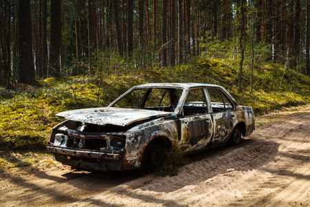 Fully burnt car in the forest in spring, accident background Stock Photo - 121890262