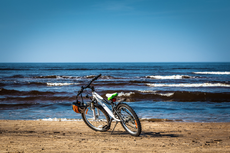 Bicycle parked next to water on Baltic beach in early spring
