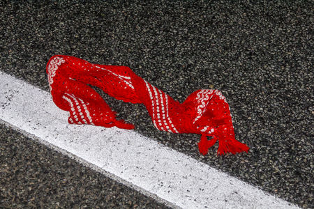 red scarf lying on a wet asphalt road at night