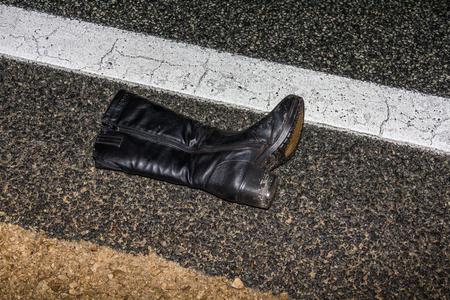 black womens boot lying on a wet asphalt road at night