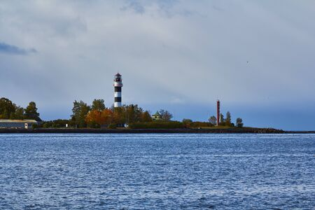 Lighthouse at the entrance to the port of Riga on windy day in autumn