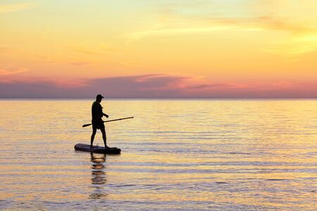 SUP boarding tour of the Gulf of Riga in the summer at sunset next to Tuya at rocky seashore of Vidzeme, Latvia