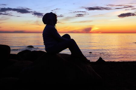 Woman is sitting on a rock by the Baltic sea and looking at the sunset Stock Photo