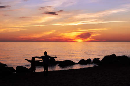 Children are standing by the Baltic sea and looking at the sunset
