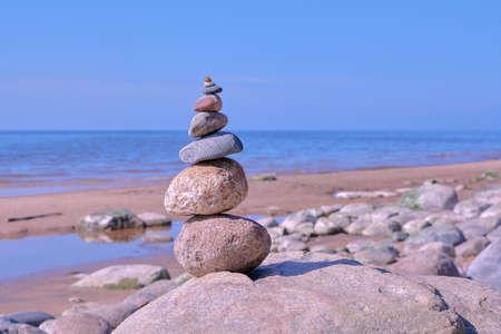 Zen balance of stones at rocky seashore of Baltic sea on sunny day