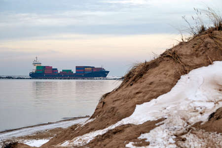 Cargo ship next to the entrance to the port of Riga, Latvia in winter
