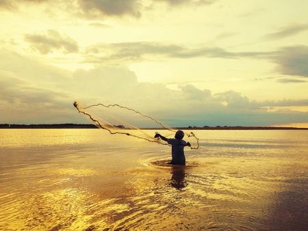 red: A medida que el sol se pone este pescador solitario es todo inmerso en el color dorado de la puesta de sol