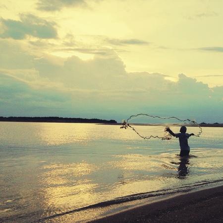 red: Un solitario pescador con su red como se pone el sol
