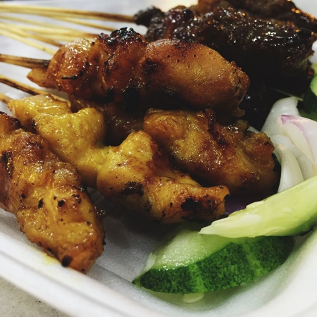 grill: Satay can be eaten at any time of the day. Its grilled meat, usually either chicken or beef. Eaten with peanut sauce and rice cubes sometimes Stock Photo