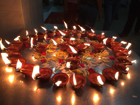 Oil lamps are lighted up for prayers in a Hindu prayer ceremony Stock Photo