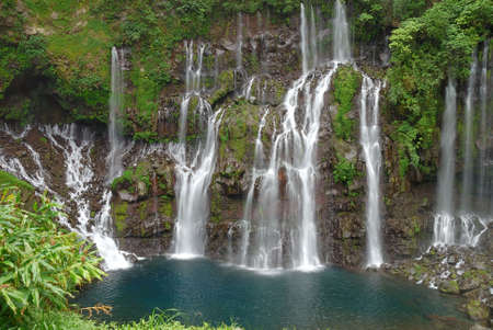 green vegetation: White waterfalls with green vegetation and blue water Stock Photo