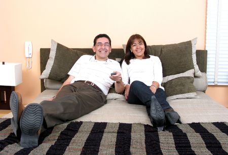 Happy couple relaxing and watching tv on the bed  photo