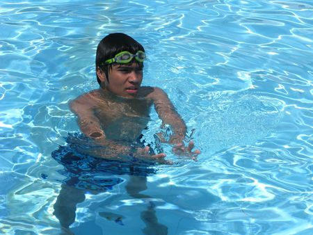 Teenage boy swimming relax in an outdoor pool  photo