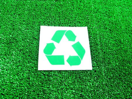 Recycle symbol over white and green grass photo