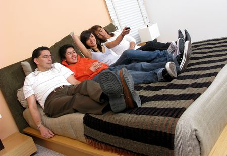 Family reclining in bed smiling at television Stock Photo - 5966503
