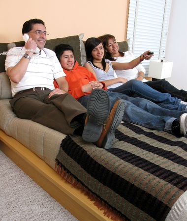 Family reclining in bed smiling at television Stock Photo - 6012426