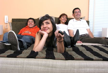 Family reclining in bed smiling at television