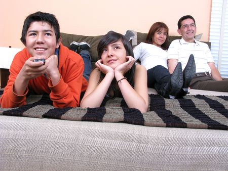 Family reclining in bed smiling at television Stock Photo - 6354757