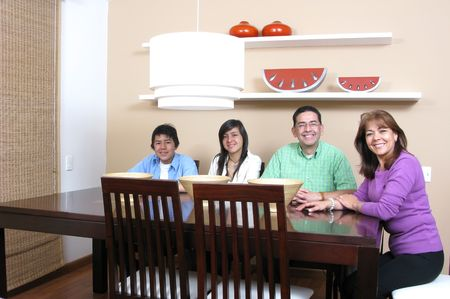Happy family enjoying mealtime together smiling, four persons. photo