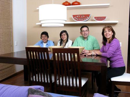 Happy family  enjoying mealtime together smiling, four persons. Stock Photo - 6376926