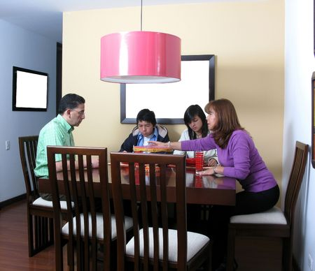 Happy family enjoying mealtime together smiling, four persons. Stock Photo - 6376943