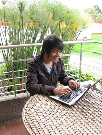Portrait of a young using laptop outdoors photo