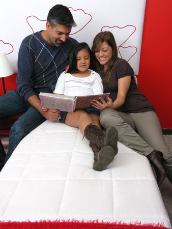 Family reclining in bed reading book together