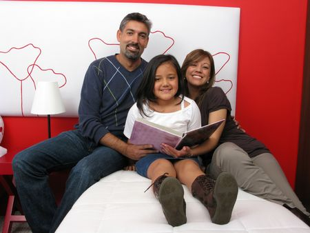 Family reclining in bed reading book together Stock Photo - 6410157