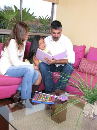 Family of three reading together the book.   photo