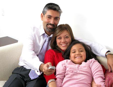 ni�os latinos: Hermosa familia feliz con control remoto de TV  Foto de archivo