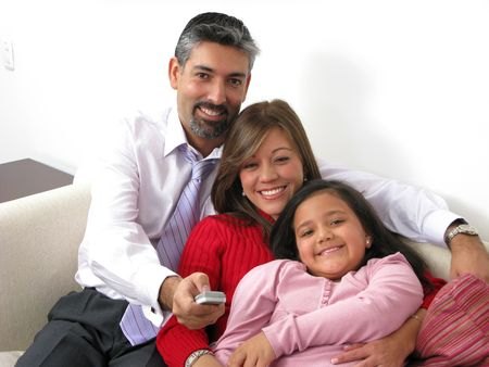 Portrait of a smiling family watching TV in the living room Stock Photo - 6689528