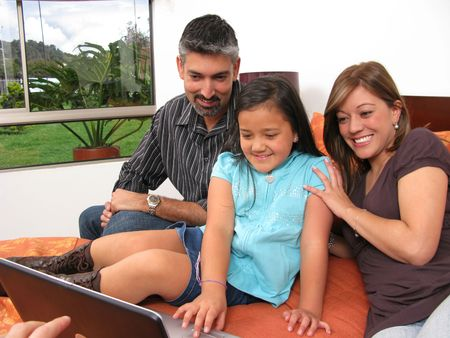 Father and children lying on the bed at home and looking into a portable computer photo