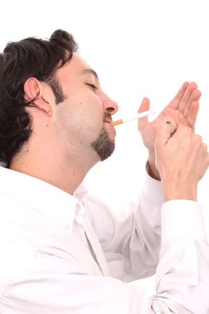 Young businessman lighting a cigarette and looking at camera photo