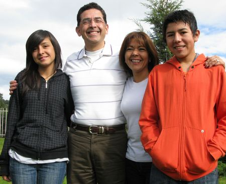 nios hispanos: Familia de cuatro que se asienta sobre hierba contra la casa