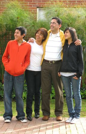 Family from four stands on grass against house photo