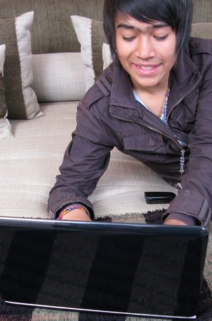 Young relaxing on the bed with laptop in her home photo