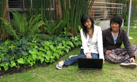 Boy and girl working on laptop in nature photo