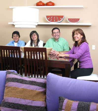 Happy family  enjoying mealtime together smiling, four persons. Stock Photo - 7413884