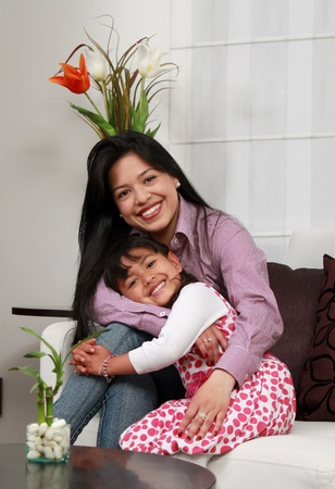 mother and girl smiling in the living room  Stock Photo