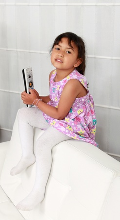 Four years old girl sitting on white sofa in front of television Stock Photo - 12868313