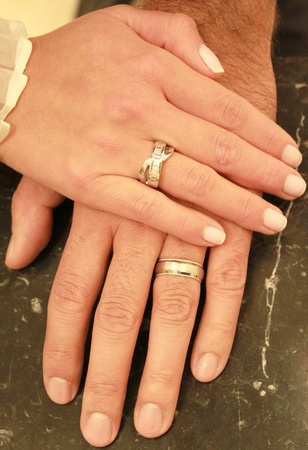 boy and girl holding hands: A couple holding hands together with their rings showing