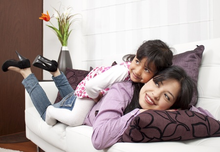 lifestyle home: Woman and young girl lying in sofa smiling